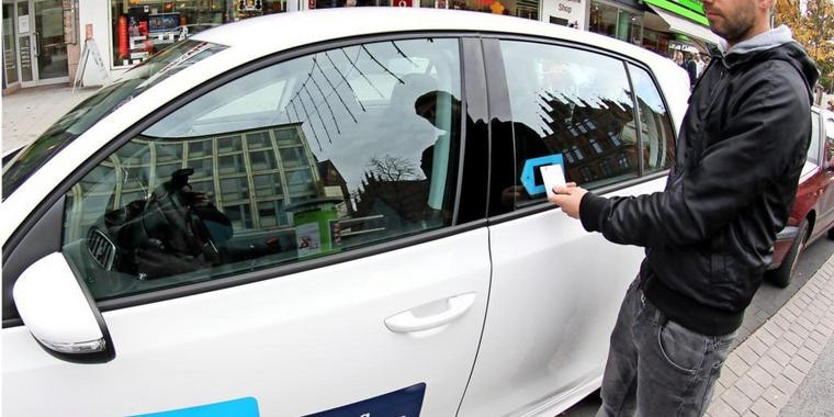 A Man Is Unlocking A Carsharing Vehicle With RFID Card
