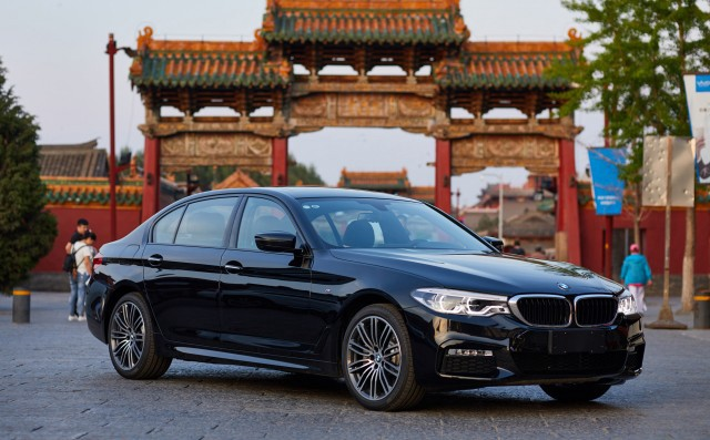 A BMW Is Parked In Front Of Chinese City Gates