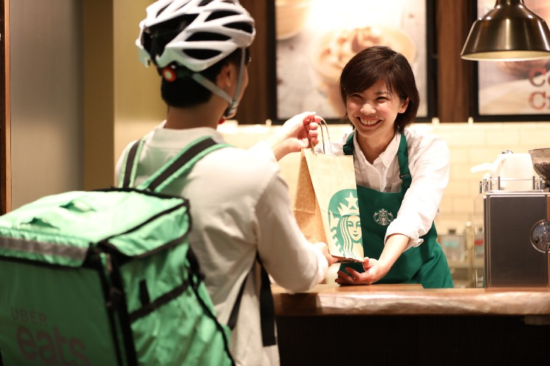 A Woman At Starbucks Is Giving A Paper Bag To UberEats Driver