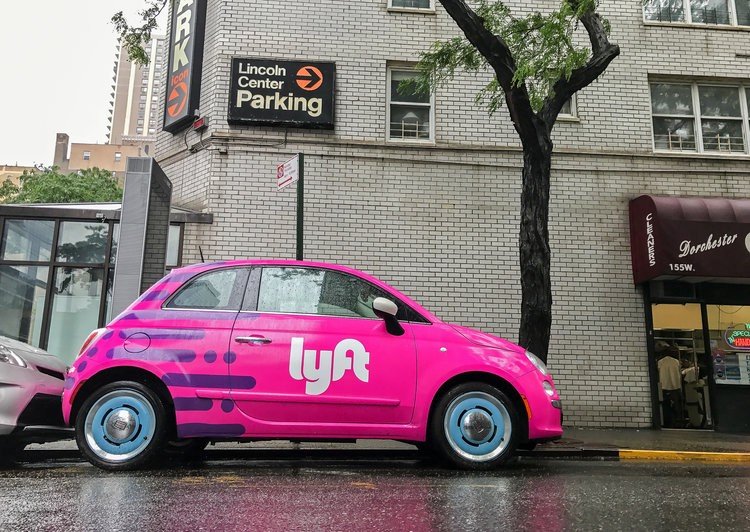 A Pink Lyft Car Is Parked Next To A Cleaning Store