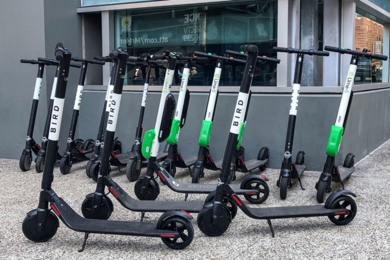 Bird And Lime Electric Scooters Parked Near A Building