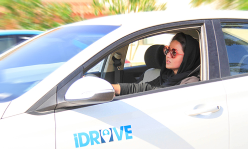 A woman is driving iDrive shared car in Saudi Arabia